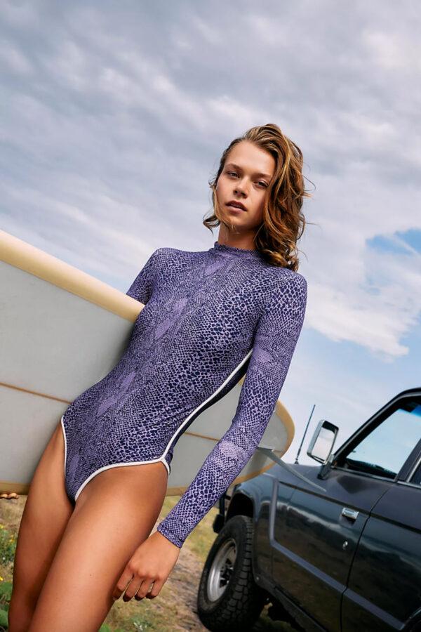 woman with surfboard wearing long sleeve swimsuit