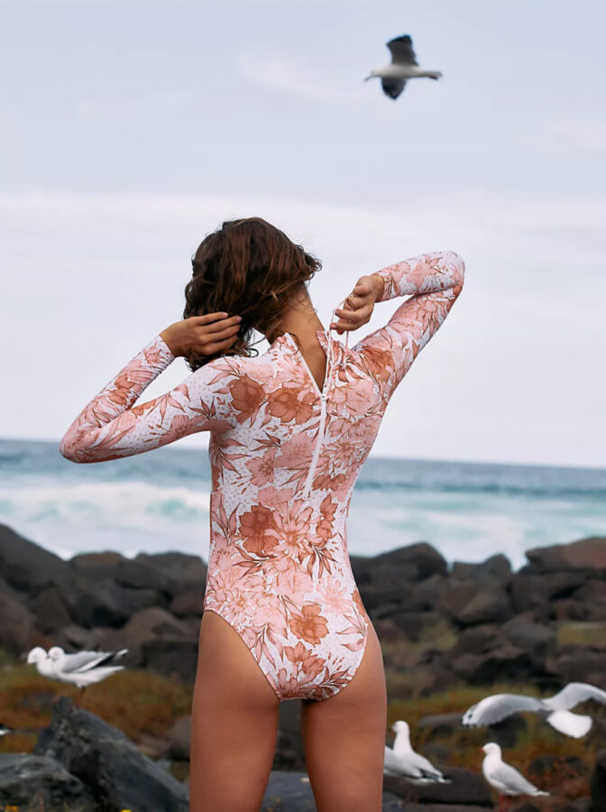 woman at beach wearing long sleeve swimsuit