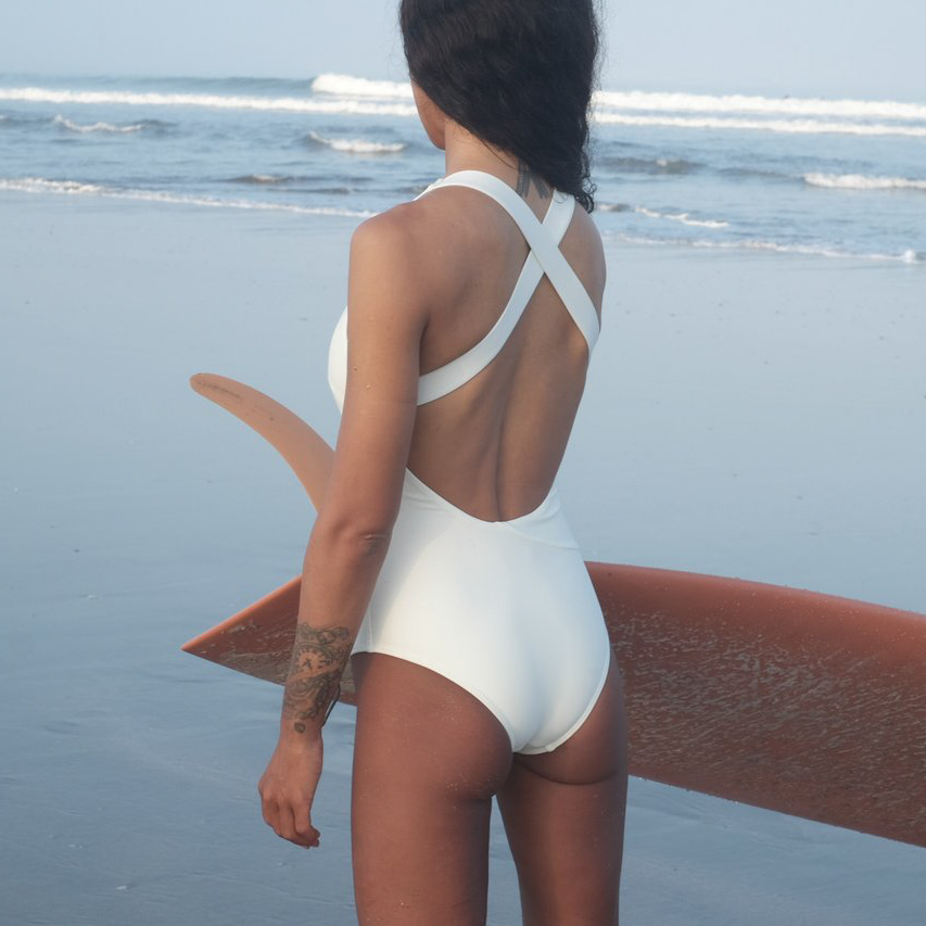woman at beach wearing white surf suit