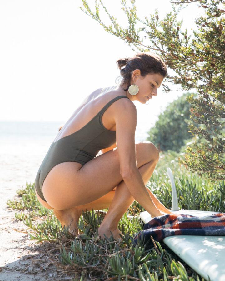 woman at beach wearing one piece surf swimwear