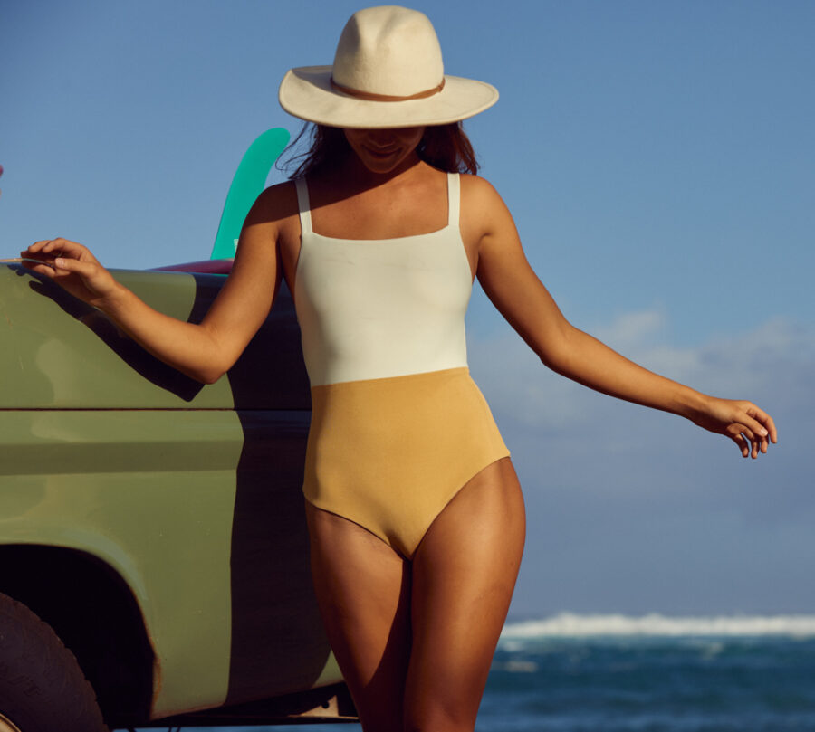 woman wearing one piece surf suit in white and yellow
