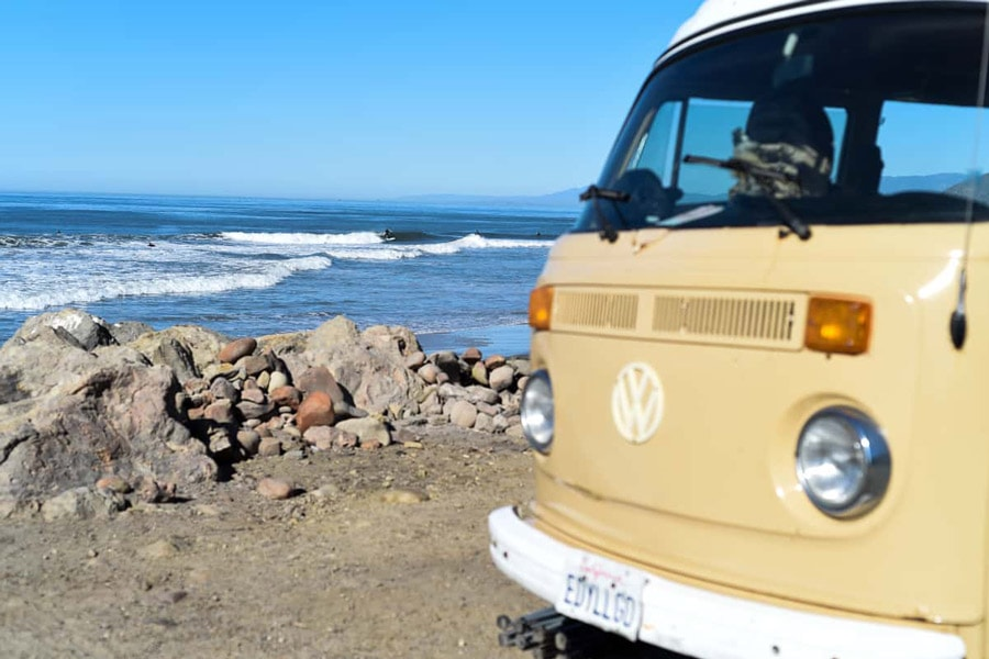 vw camper bus with surfer in background