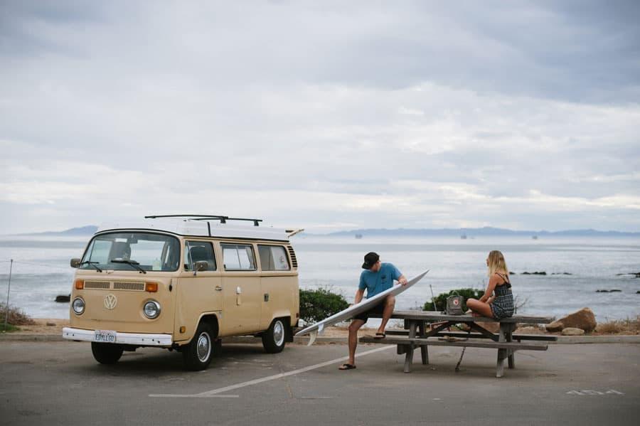 vintage vw bus surfer waxing surfboard picnic table carpinteria