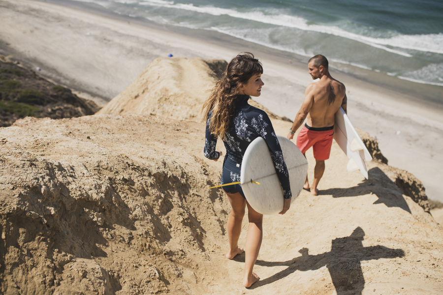 man and woman walking with surfboards wearing Vuori clothing