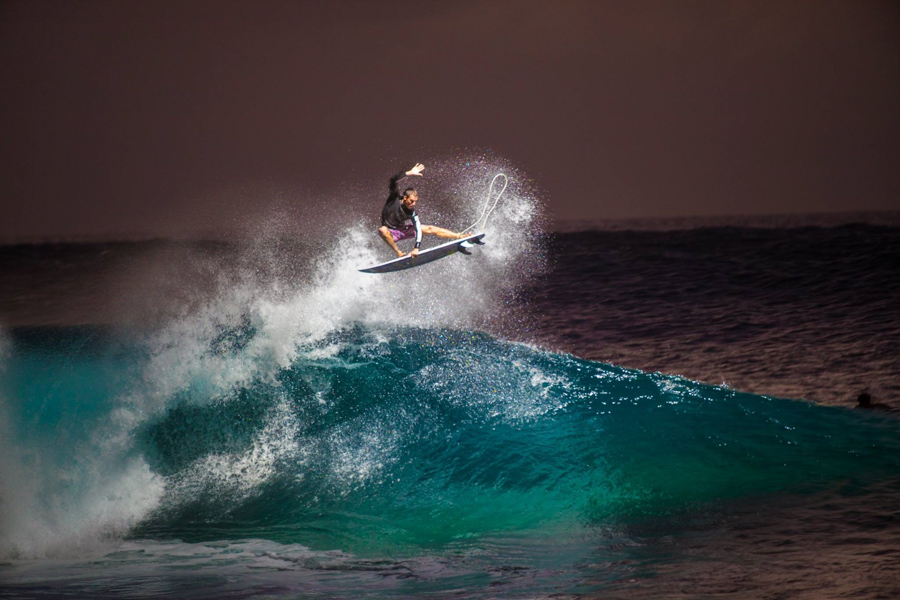 Surfer performing air maneuver on large wave at night - by Volcom surf brand