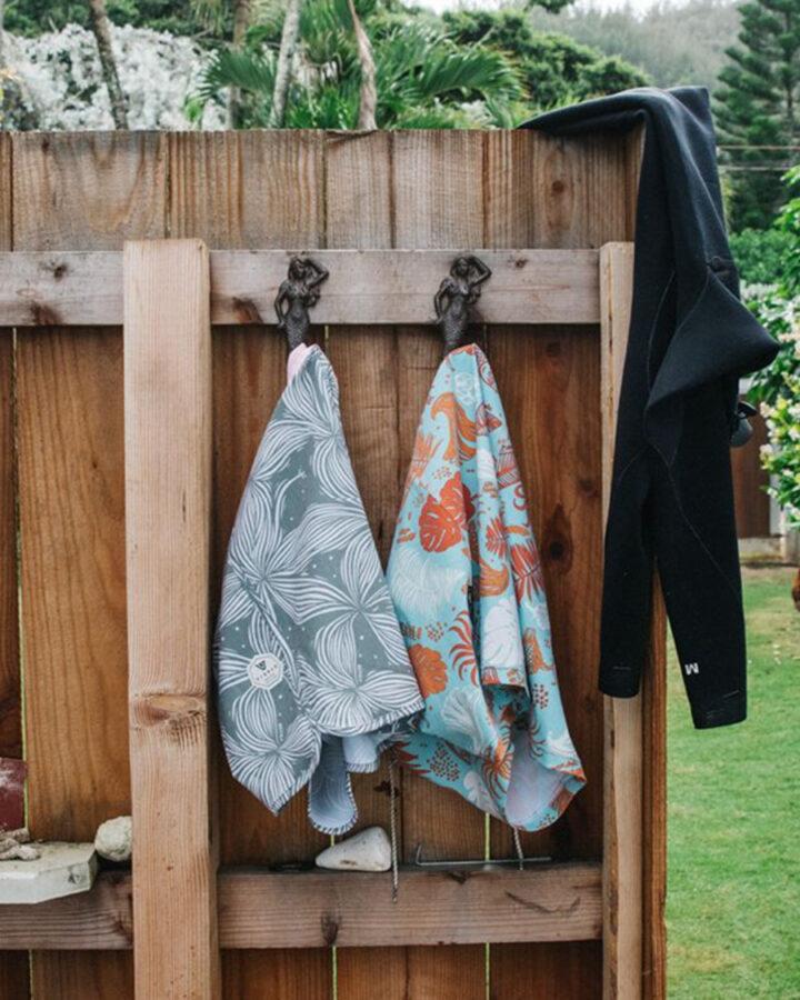 boardshorts by Vissla surf brand hanging on wood fence