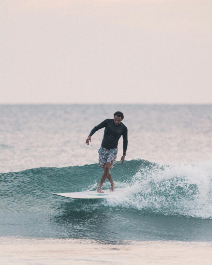 man surfing wave and wearing boardshorts by surf brand howler brothers