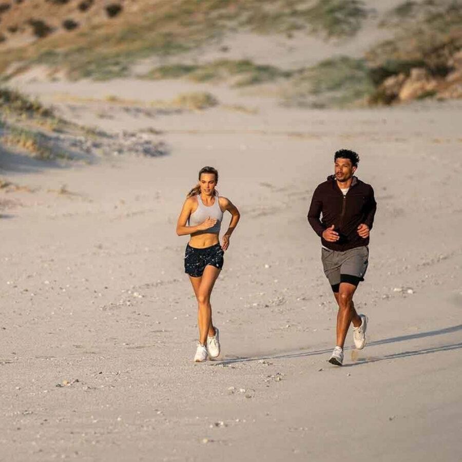man and woman jogging on beach - wearing california surf brand Vuori