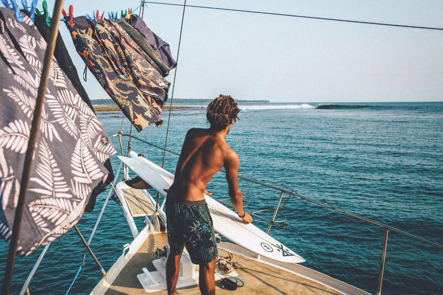 surfer on boat scouting waves wearing boardshorts by surf brand Roark Revival