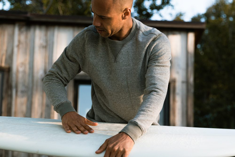 man holding surfboard wearing sweater by wellen surf company