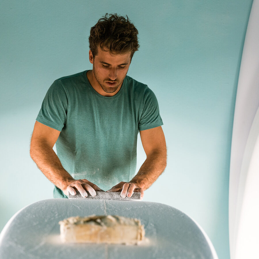 man shaping surfboard wearing hemp t-shirt by wellen