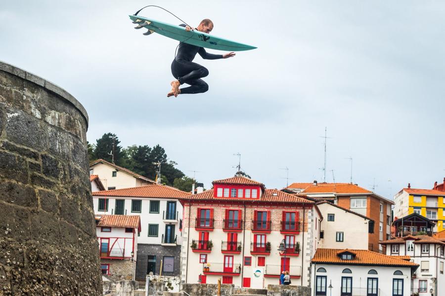 surfer jumping into ocean wearing patagonia wetsuit