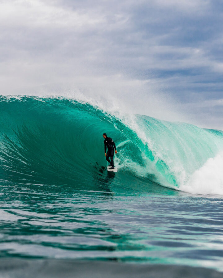 surfer in barrel wearing wetsuit by rip curl surf company