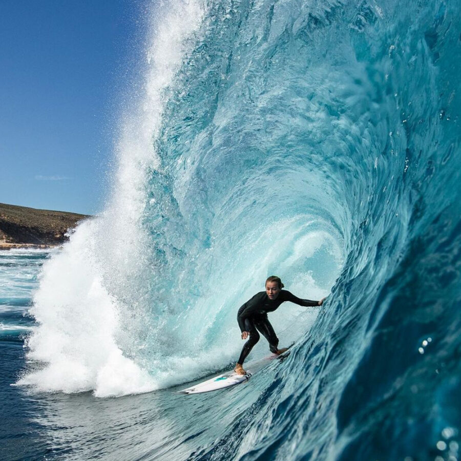 woman surfing large wave wearing a oneill wetsuit