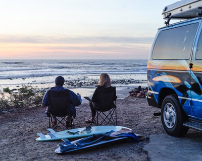 surfers sitting in camping chairs looking at surf
