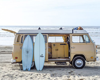 california campervan rentals vintage yellow vw with surfboards on it