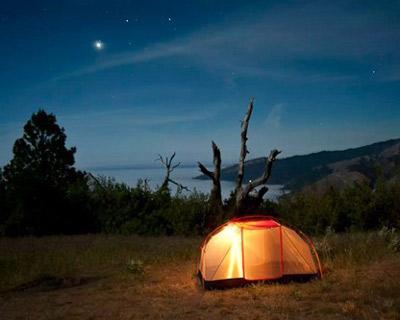 glowing tent under moonlight sky
