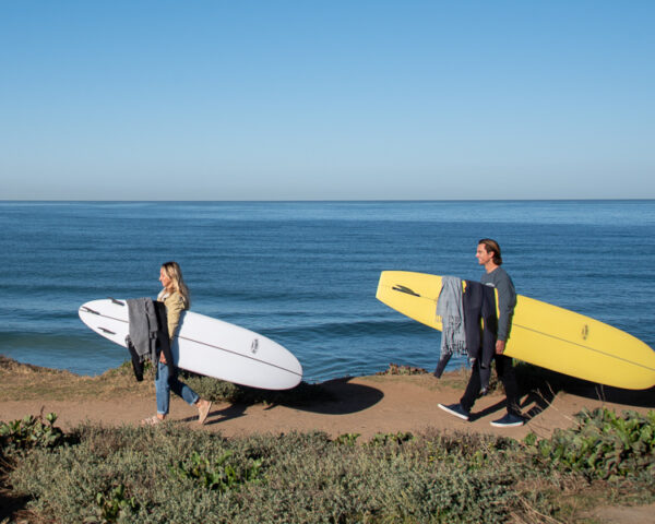 two beginner surfers with surfboards walking along the ocean to go surfing