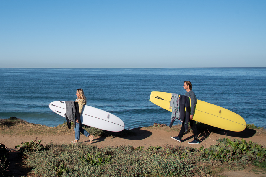 beginner surfers with surfboards walking to the beach to learn how to surf