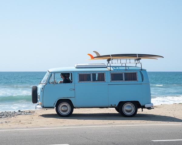 blue vintage vw campervan rental at beach with surfboards on top