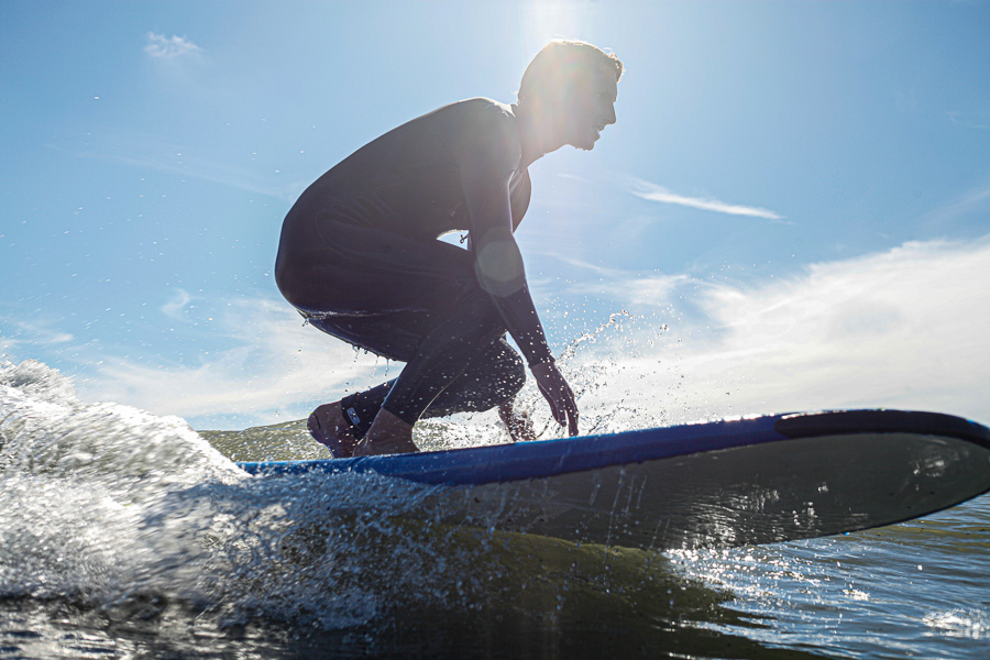 man learning how to surf on beginner surfboard