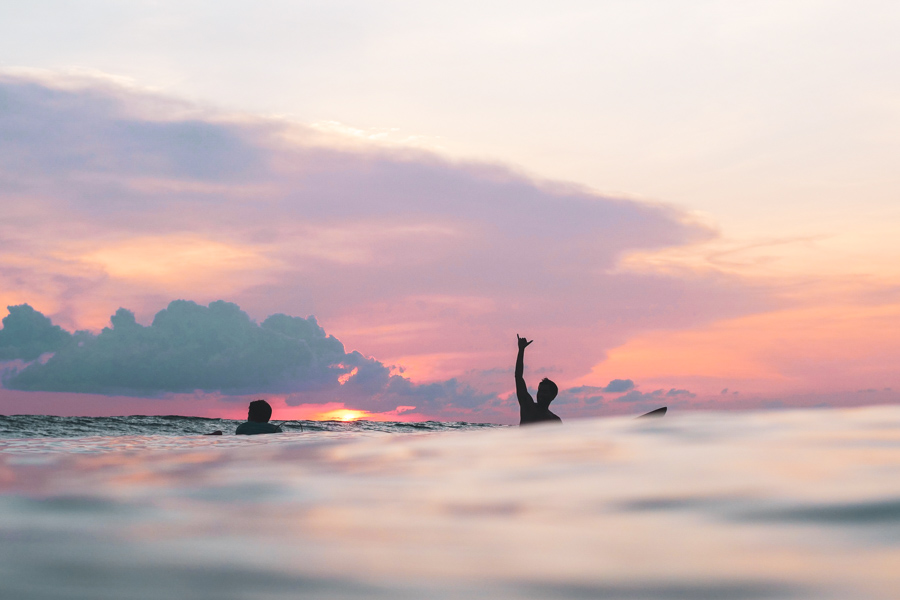 surfer giving shaka sign in the ocean at sunset