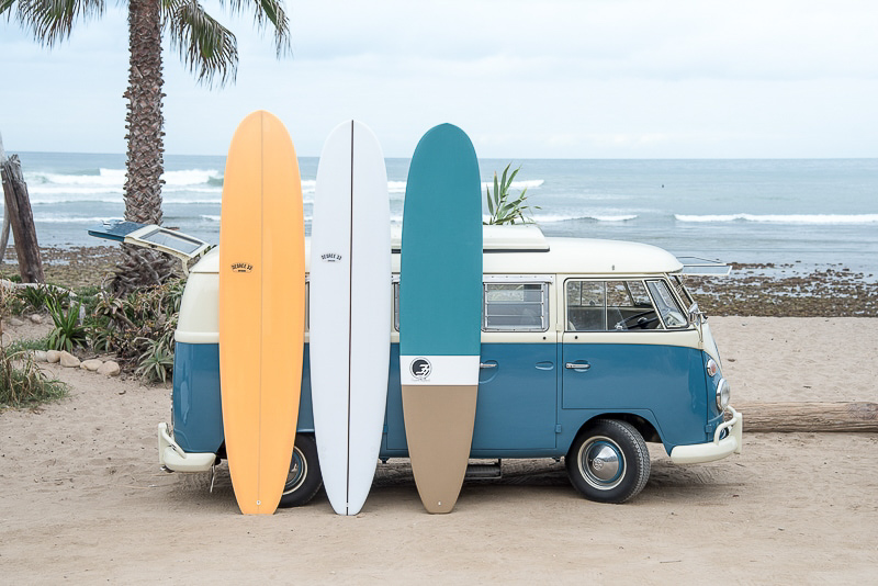 longboard surfboards with vw bus at the beach