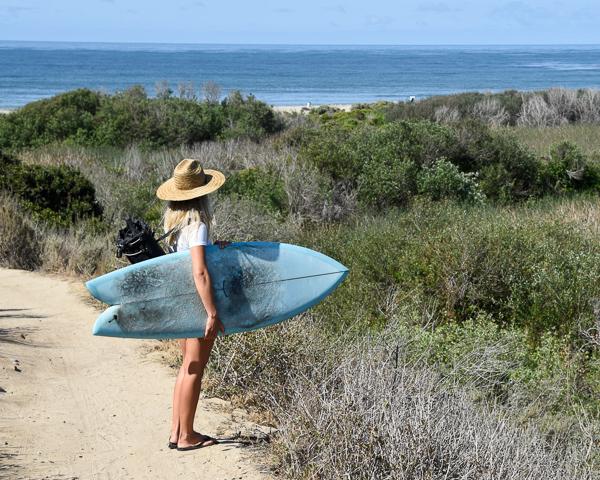 female surfer holding fish shortboard overlooking trestles