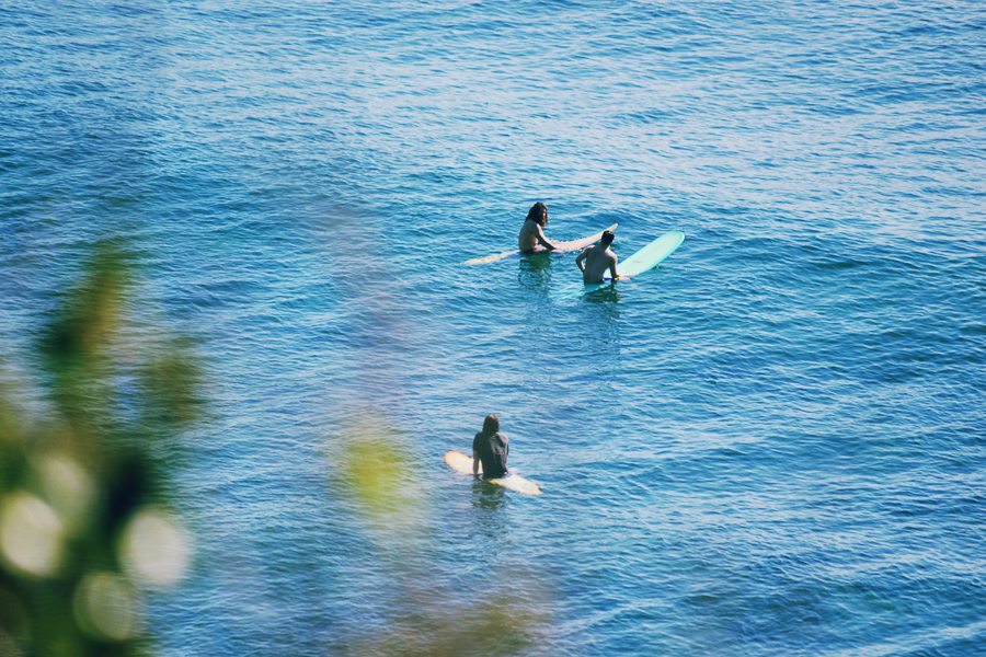 three beginner surfers sitting in the ocean waiting for waves