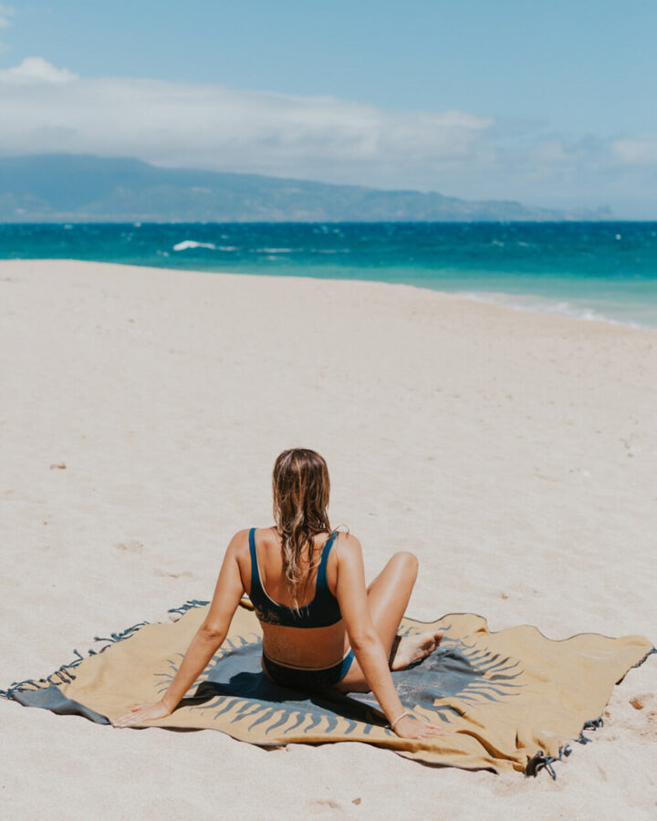 girl in bikini sitting on cute beach blanket on the beach