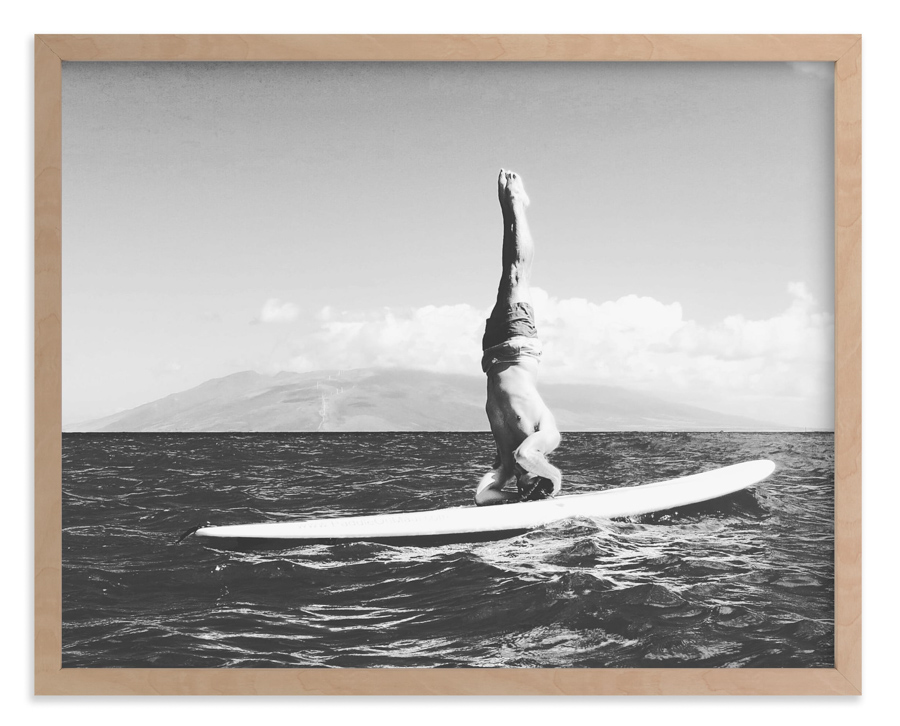 Vintage style surf photo of a man doing a shoulder stand on a surfboard