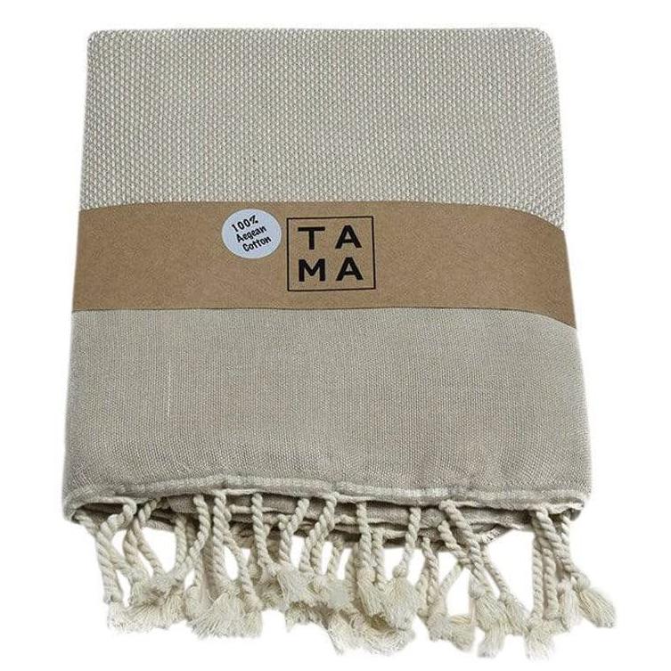 beige beach towel with white tassels