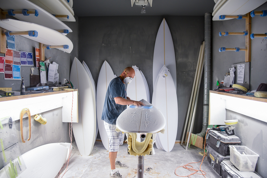 A surfboard shaper in a shaping bay shaping a surfboard