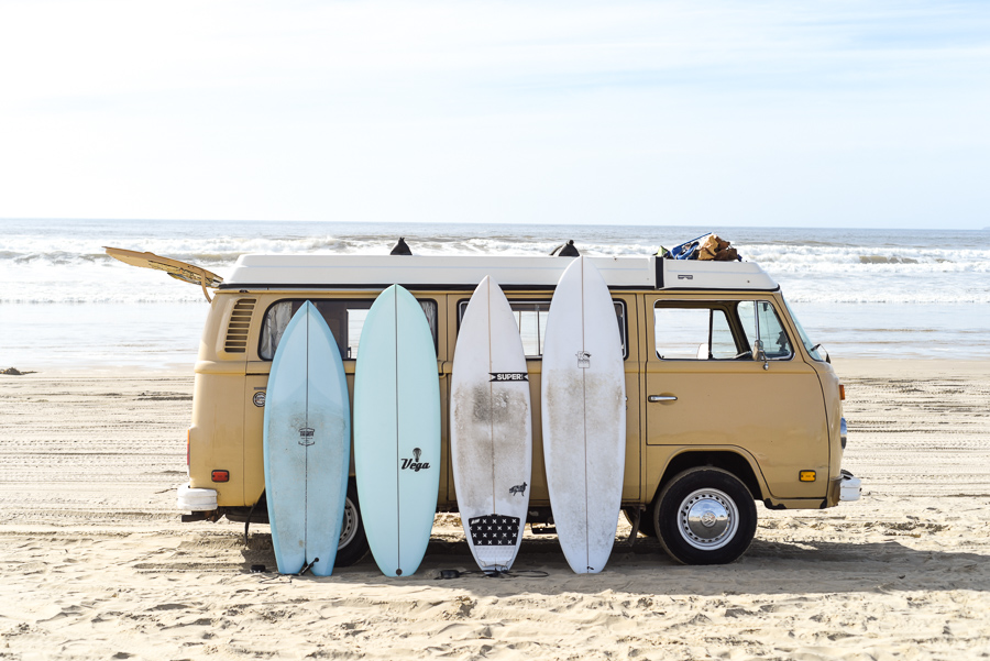 Surfboards of different sizes lined up on a VW bus on the beach