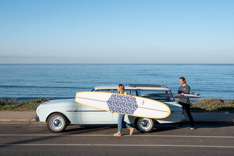 Woman carrying a longboard next to vintage car and ocean