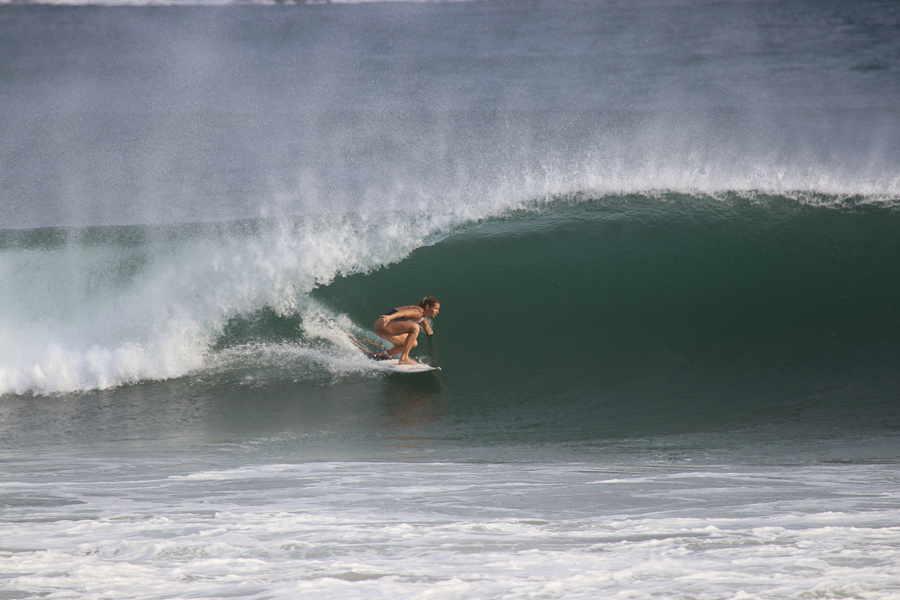 Woman surfing a barrel - How to choose a surfboard depends on the type of waves you want to surf