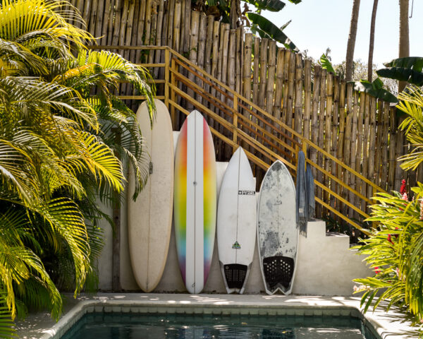 Four colorful surfboards of multiple different sizes lined up at the side of a pool